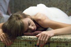 Mujer joven en el hammam o el baño turco que tiene tiempo hermoso imagenes de archivo