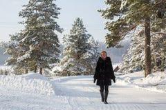 Mujer joven en el invierno en el pueblo ruso nevoso El caminar Foto de archivo libre de regalías