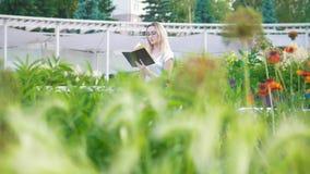 Mujer joven en el jardín con las flores que se sientan en el banco que lee un libro almacen de video
