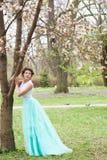mujer joven en el jardín de la primavera, vestido largo que lleva Imagen de archivo