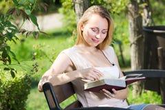 Mujer joven en el libro de lectura del banco Foto de archivo libre de regalías