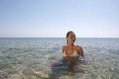 Mujer joven en el mar tranquilo. Foto de archivo libre de regalías