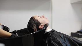 Mujer joven en el marco, fregadero del pelo del lavado del peluquero almacen de video