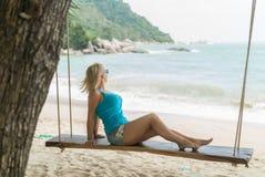 Mujer joven en el oscilación en una playa Fotografía de archivo libre de regalías