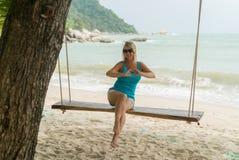 Mujer joven en el oscilación en una playa Imagenes de archivo
