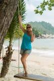 Mujer joven en el oscilación en una playa Imagen de archivo libre de regalías