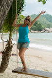Mujer joven en el oscilación en una playa Fotos de archivo libres de regalías