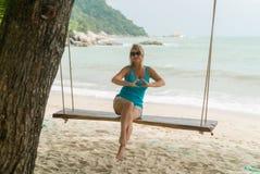 Mujer joven en el oscilación en una playa Fotografía de archivo