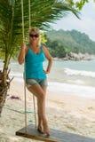 Mujer joven en el oscilación en una playa Foto de archivo