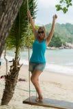 Mujer joven en el oscilación en una playa Imagen de archivo