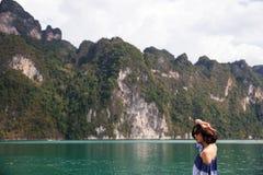 Mujer joven en el paño del verano que se coloca y que mira al océano imágenes de archivo libres de regalías