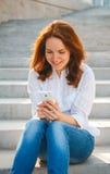 Mujer joven en el parque con el teléfono Imagen de archivo libre de regalías