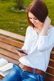 Mujer joven en el parque con el teléfono Fotografía de archivo libre de regalías