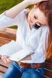 Mujer joven en el parque con el teléfono Foto de archivo libre de regalías