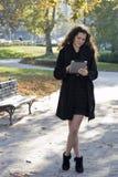Mujer joven en el parque con PC de la tablilla Imagen de archivo