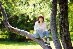 Mujer joven en el parque de la primavera Fotos de archivo libres de regalías