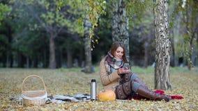 Mujer joven en el parque del otoño que manda un SMS en el teléfono metrajes