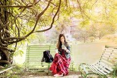 Mujer joven en el parque que se sienta en un banco Fotos de archivo libres de regalías