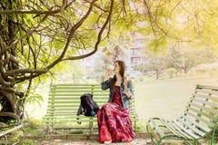 Mujer joven en el parque que se sienta en un banco Fotos de archivo