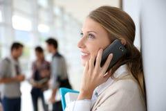 Mujer joven en el pasillo de la universidad que habla en el teléfono Fotografía de archivo libre de regalías