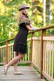 Mujer joven en el pequeño puente de madera Foto de archivo