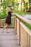 Mujer joven en el pequeño puente de madera Imagen de archivo libre de regalías