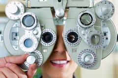 Mujer joven en el phoropter para la prueba del ojo Fotos de archivo libres de regalías
