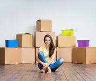 Mujer joven en el piso al lado de las cajas de cartón Imágenes de archivo libres de regalías