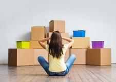 Mujer joven en el piso al lado de las cajas de cartón Imagen de archivo libre de regalías