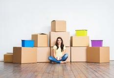 Mujer joven en el piso al lado de las cajas de cartón Fotografía de archivo