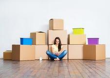 Mujer joven en el piso al lado de las cajas de cartón Fotografía de archivo libre de regalías