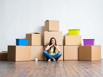 Mujer joven en el piso al lado de las cajas de cartón Fotos de archivo libres de regalías