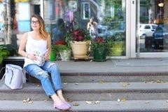 Mujer joven en el piso en la calle que mira in camera usando p Imagen de archivo