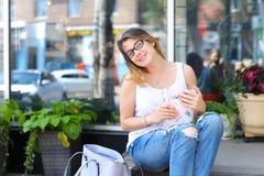 Mujer joven en el piso en la calle que mira in camera usando p Foto de archivo
