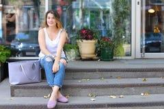 Mujer joven en el piso en la calle que mira in camera usando p Imagen de archivo libre de regalías