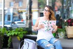 Mujer joven en el piso en la calle que mira in camera usando p Imágenes de archivo libres de regalías
