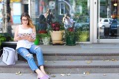Mujer joven en el piso en la calle que mira in camera usando p Foto de archivo libre de regalías