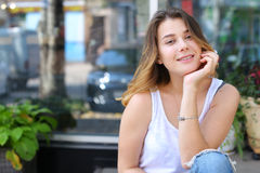Mujer joven en el piso en la calle que mira in camera usando p Fotos de archivo