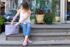Mujer joven en el piso en la calle que mira in camera usando p Fotografía de archivo