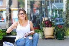 Mujer joven en el piso en la calle que mira in camera usando p Fotografía de archivo libre de regalías