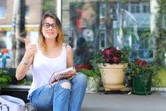 Mujer joven en el piso en la calle que mira in camera usando p Imagenes de archivo