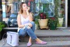 Mujer joven en el piso en la calle que mira in camera usando p Fotos de archivo libres de regalías