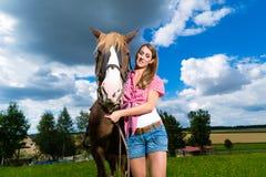 Mujer joven en el prado con el caballo fotos de archivo
