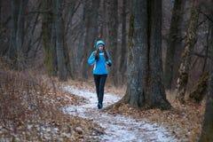 Mujer joven en el rastro que corre en parque del invierno Imagenes de archivo