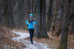 Mujer joven en el rastro que corre en parque del invierno Foto de archivo libre de regalías