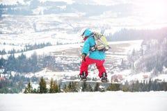Mujer joven en el salto de la snowboard Fotos de archivo