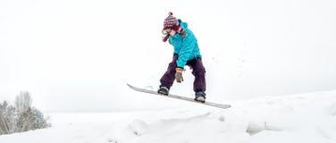 Mujer joven en el salto de la snowboard Foto de archivo