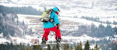 Mujer joven en el salto de la snowboard Foto de archivo libre de regalías