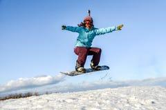 Mujer joven en el salto de la snowboard Fotos de archivo libres de regalías