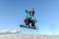 Mujer joven en el salto de la snowboard Imagenes de archivo